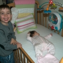 Cousin Max with Sara in her crib